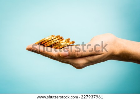 Hand holding golden coins concept on blue background. Taxpayer business concept. - stock photo