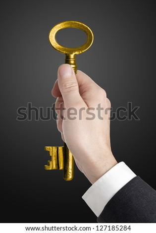Hand holding golden key to success over black background