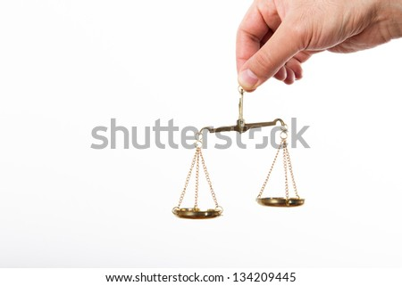 Hand holding golden scales of justice, isolated on white background. - stock photo