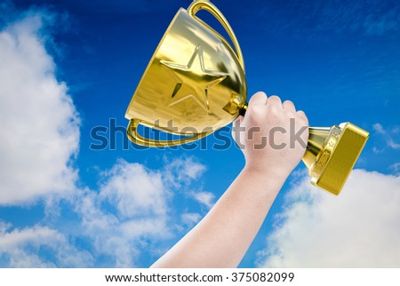 hand holding golden trophy with blue sky background - stock photo