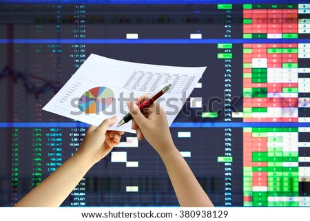hand holding graph paper with blur image of graph stock market