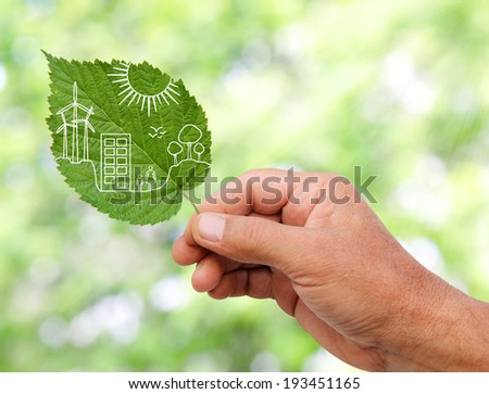 hand holding Green city concept, cut the leaves of plants - stock photo