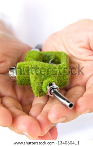 hand holding green fuel nozzle - stock photo