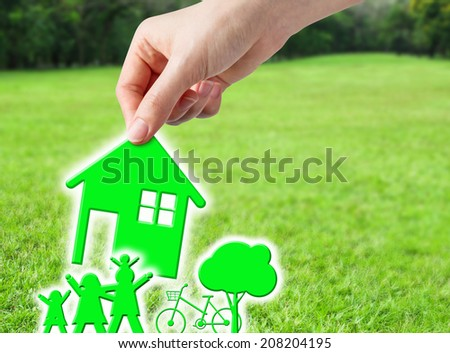 Hand holding green home