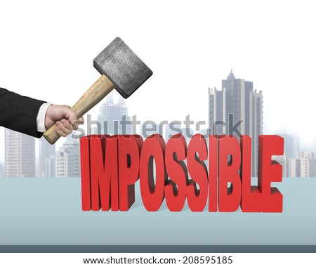 Hand holding hammer to crack impossible 3D word in office - stock photo