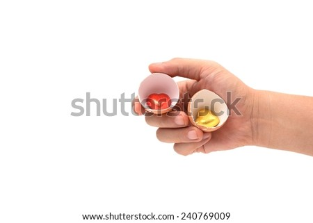 hand holding heart on egg shells  isolated on white - stock photo