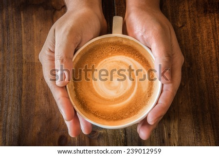Hand holding hot cup of coffee - stock photo