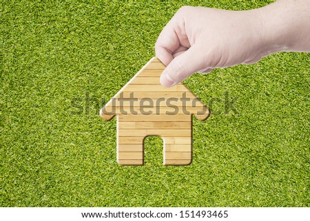 Hand Holding House Icon made from wood. Concept for business and buying a house