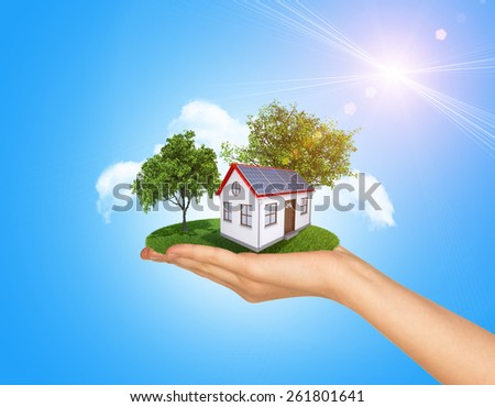 Hand holding house on green grass with tree and solar panels. Background clouds and blue sky - stock photo