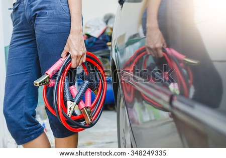 Hand holding jumper cable for recharge the battery car - stock photo
