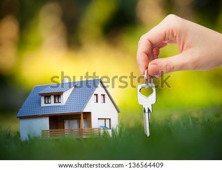 hand holding key against house background - stock photo