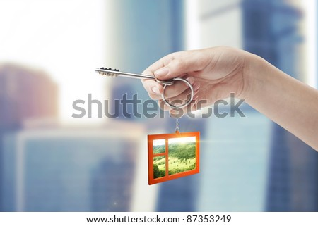 Hand holding key with a keychain in the shape of the window. Beautiful view behind a window of a green field with a blue sky. House key - stock photo