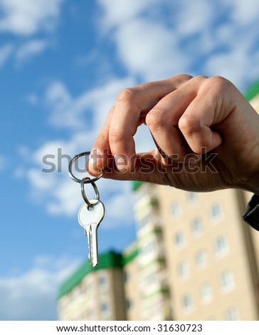 hand holding keys, house in the background - stock photo