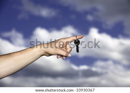 Hand holding keys with blue sky and clouds in background