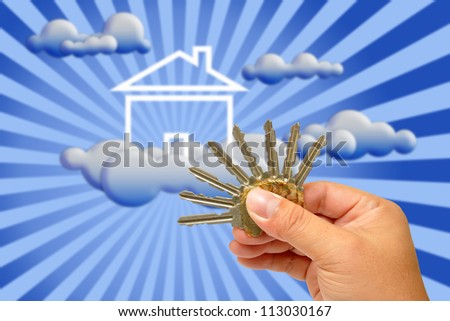 Hand holding keys with house in the background