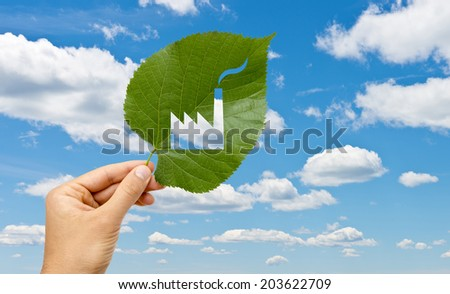 Hand holding leaf with a factory cutted against blue sky - stock photo