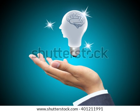 Hand holding light bulb head - stock photo