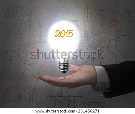 hand holding 2015 light bulb illuminated dark doodles wall with business concept graph background - stock photo