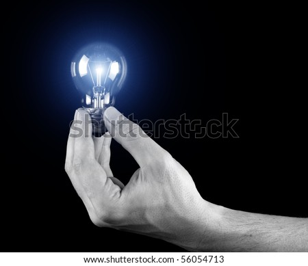 Hand holding light bulb isolated on black - stock photo