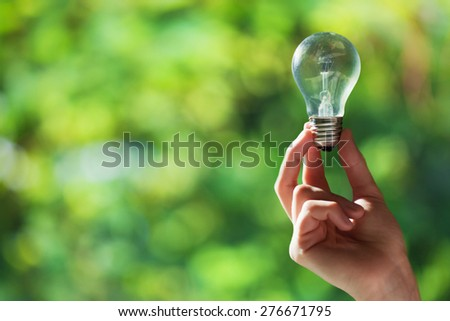 Hand holding light bulb on green nature background with space for text - stock photo