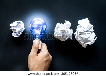 Hand holding light bulb with crumpled office paper - stock photo