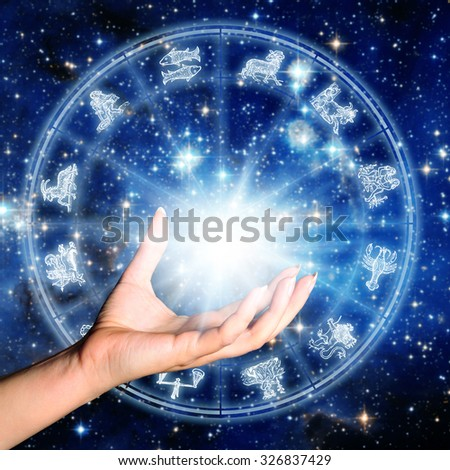 hand holding light in front of an astrology wheel with zodiac signs - stock photo
