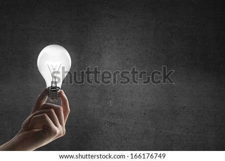 hand holding lightbulb on a concrete background - stock photo