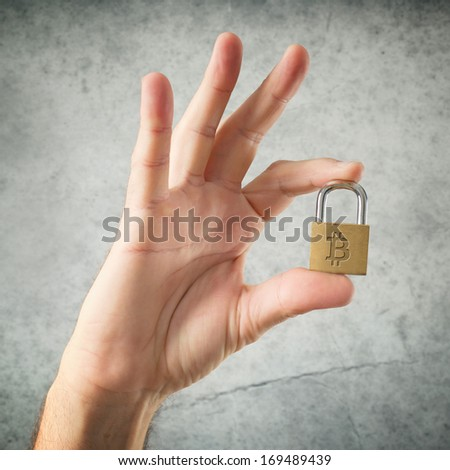 Hand holding locked padlock with Bitcoin symbol. Security and insurance concept. - stock photo