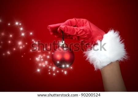 Hand holding magic Christmas ball - stock photo