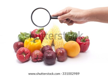 Hand holding magnifier glass focused on healthy food - stock photo