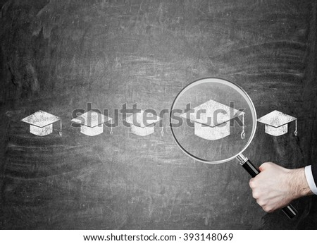 Hand holding magnifier over red picture of academic hat in row of hats. Chalk board background. Concept of choice. - stock photo