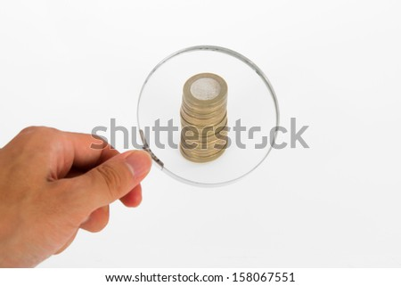 Hand holding magnifying glass and focused on coins, isolated on white background. - stock photo