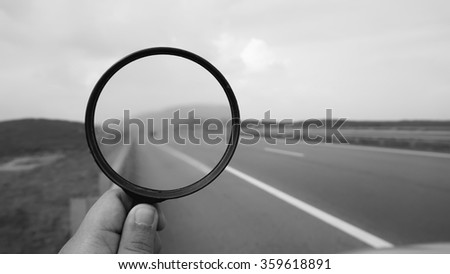 hand holding magnifying glass in black and white on a free highway. nature composition                                 - stock photo