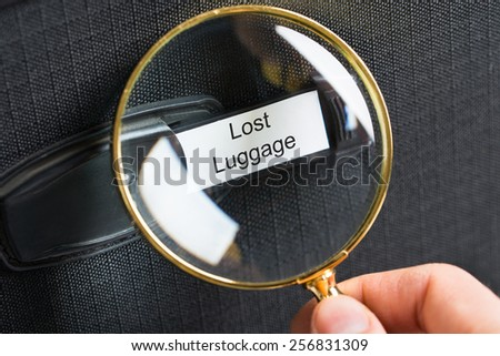 Hand Holding Magnifying Glass On Travel Bag With A Lost Luggage Label - stock photo