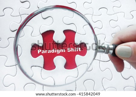 Hand holding magnifying glass over jigsaw puzzle with word Paradigm Shift - stock photo
