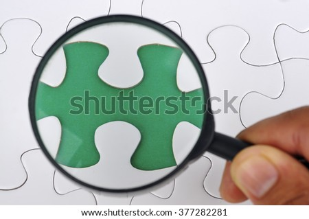 Hand Holding Magnifying Glass Searching Missing Puzzle Pieces - stock photo