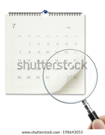 Hand holding magnifying glass to checking calendar  - stock photo