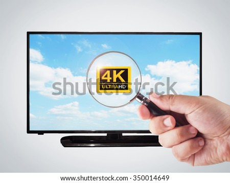 hand holding magnifying glass with 4k television display - stock photo