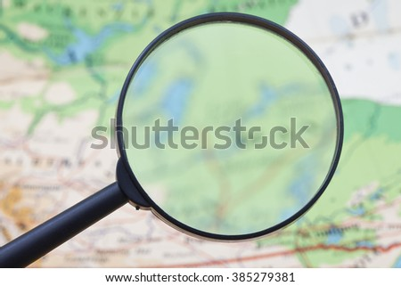 Hand holding Magnifying glass with map background