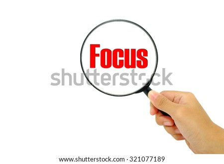 Hand holding magnifying glass with words Focus. - stock photo