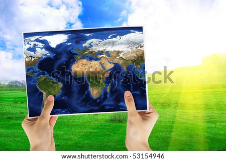 Hand holding map at beauty sunset on background - stock photo