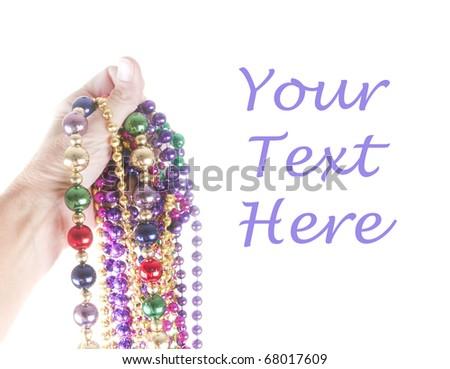Hand holding mardi gras beads - stock photo