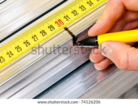 Hand holding marker pen marking measurement on a metal stud - stock photo
