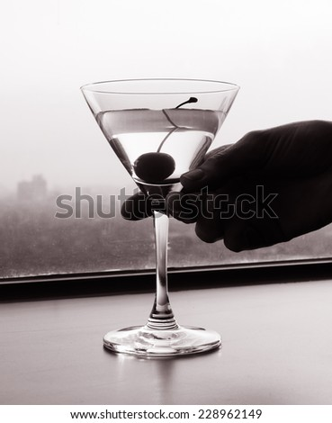 Hand holding martini glass  - stock photo