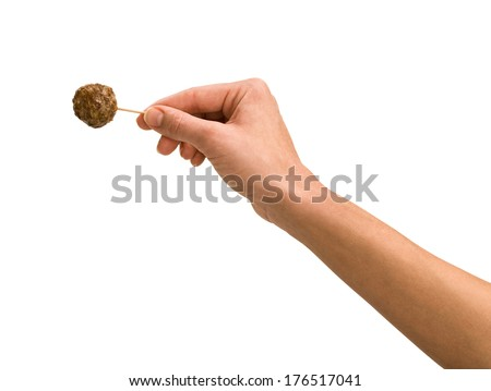 Hand Holding Meatball on Toothpick on White, hors doeuvres - stock photo