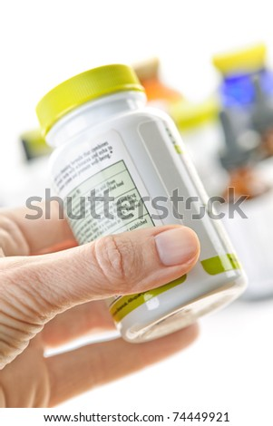 Hand holding medicine bottle to read label - stock photo