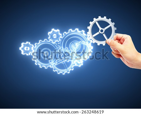 hand holding metal gear on blue background - stock photo