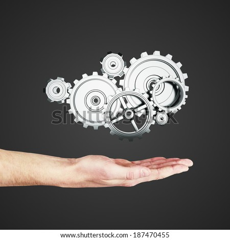 hand holding metal gears and cogwheels on black background - stock photo