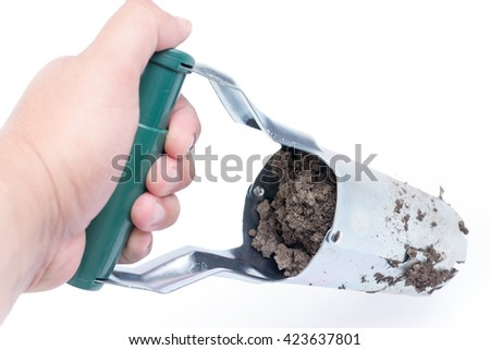 Hand holding metal tool for digging holes and planting of fruit and vegetables. - stock photo