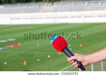 hand holding microphone for interview during a football mach - stock photo